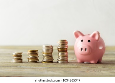 piggy bank with coin on old wooden table