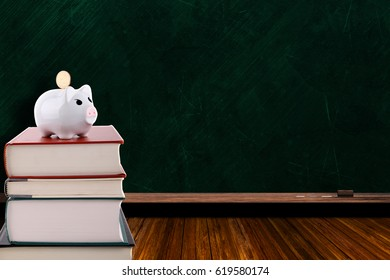 Piggy bank with coin on a stack of books on chalkboard background and copy space. Concept of saving for education and rising cost of education.