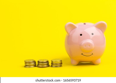Piggy bank with coin pile on yellow background, space for text. Finance, saving money. Business to success and saving for retirement concept