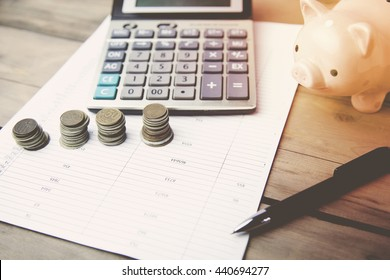 piggy bank with coins and calculator on wooden background