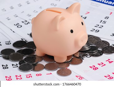 Piggy bank and coins on monthly calendar, saving money, wealth and financial for investment