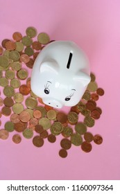 piggy bank and coins on pink background