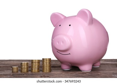 Piggy bank and coins on wooden table against white background
