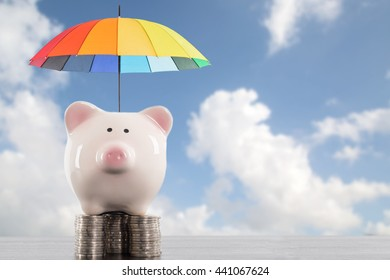 Piggy bank with colorful umbrella for saving money. Protection investment concept.