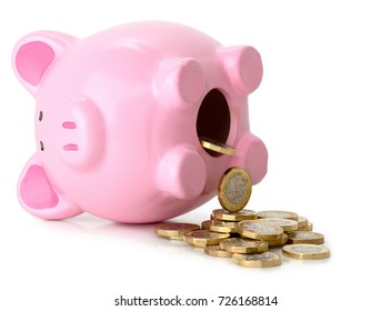 Piggy bank fallen on its side with coins pouring out isolated on a white background