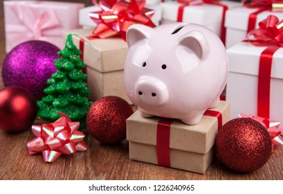 piggy bank with gift boxes and Christmas toys close up
