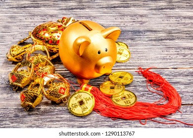 Piggy bank with golden coins and chinese ornament on the wooden table. Chinese New Year. Year of the earth pig