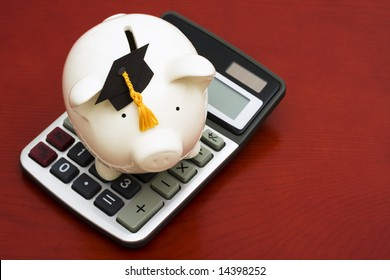 Piggy bank with graduation cap and calculator