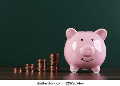 Piggy bank with growth coins against blank dark green chalkboard.