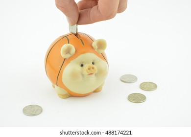 Piggy bank with a hand holding a coin on the white background. Save money.