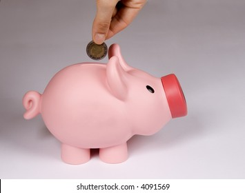 Piggy bank with hand and money.