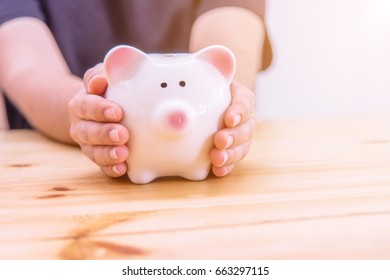 Piggy bank in hand on wooden top table, money savings concept