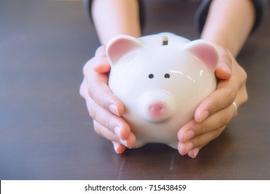 Piggy bank in hand on wooden top table, money savings concept.