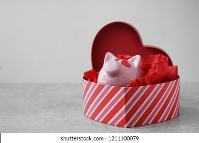 Piggy bank in heart-shaped gift box on grey background. Concept of buying presents for Valentine's day