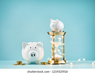 Piggy bank and hourglass wrapped in Christmas lights on a blue background.