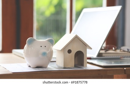 Piggy bank and house design on wooden floor. Ideas to save money on buying real estate or new loans for planned investments in future ideas.
