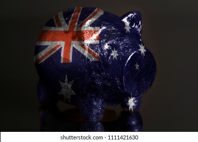 Piggy bank with IFlag of Australia on a black background.
