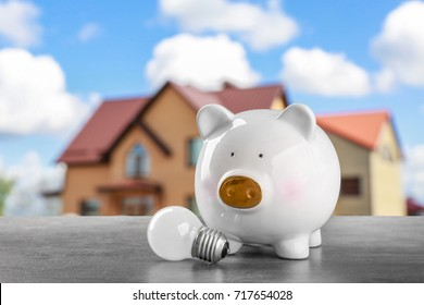 Piggy bank with light bulb on table. Concept of electric power and saving money