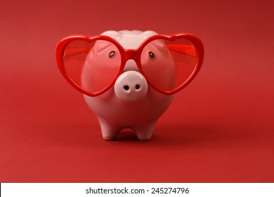 Piggy bank in love with red heart sunglasses standing on red background