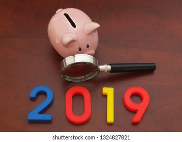 Piggy bank, magnifying glass and numbers 2019, saving money in 2019 concept