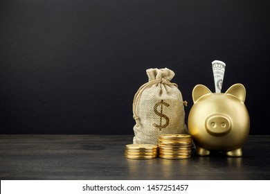 Piggy Bank and money bag with coins on dark wooden background