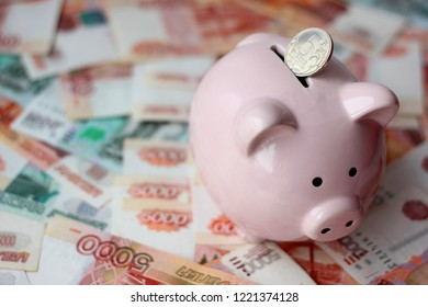 piggy bank, money Russian banknotes of dignity five thousand, one thousand rubles, metal coins 10, 5, 2, 1 ruble background, concept