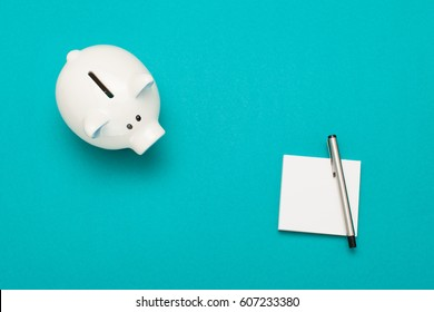 Piggy bank and notebook with a pen isolated on purple background