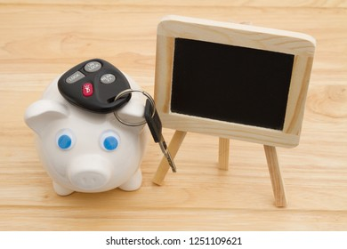 A piggy bank on a desk with blank chalkboard and car keys for your message