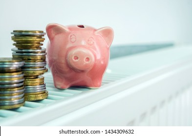 Piggy bank on a home heating radiator. Conceptual image of the high cost of heating, saving money, saving energy, energy efficiency.