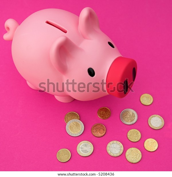 Piggy bank on pink with various Euro coinage around - shallow dof