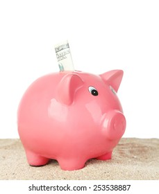 Piggy bank on sand, on white background