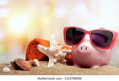 Piggy bank on sandy beach background