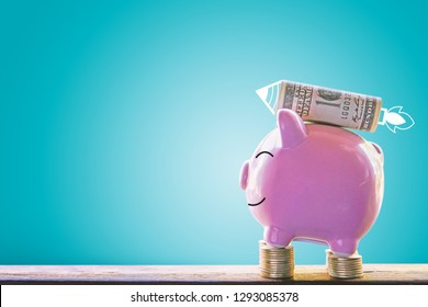 Piggy bank on wood plank with rocket icon blue background saving and growing concept.