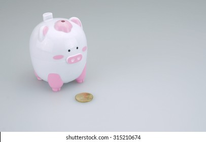 Piggy bank with one gold coin placed on white background.
