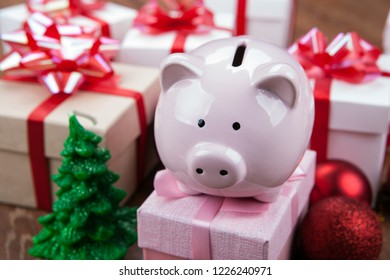piggy bank with a pink gift box against the background of Christmas toys and gift boxes