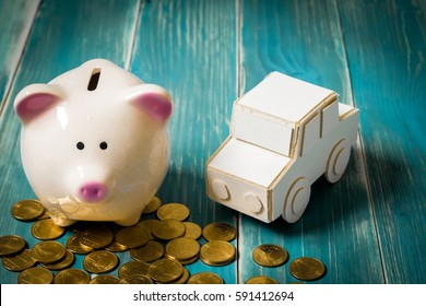 A piggy bank put on the stacking gold coins and car model on the vintage blue background, saving money for buying or loan for planned investment in the future concept.