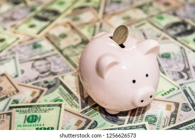 Piggy bank with Quater dollar coin on background of dollar bills, savings and investments concept