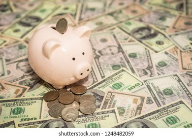 Piggy bank with Quater dollar coins on background of dollar bills, savings and investments concept