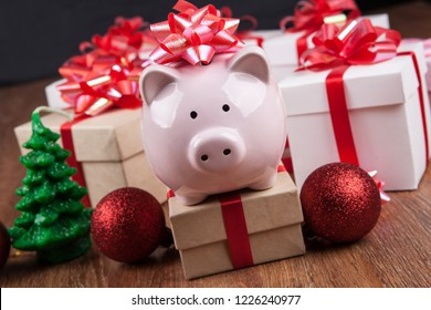 piggy bank with red bow against the background of gift boxes and Christmas toys close up