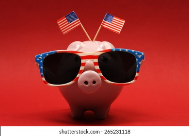 Piggy bank with retro sunglasses with USA flag and two small USA flags on red background