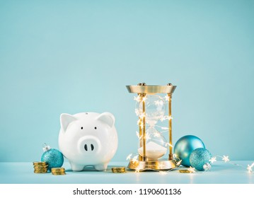 Piggy bank and rustic hourglass wrapped in lights on a blue background. Countdown to save for the Christmas gift giving season concept.