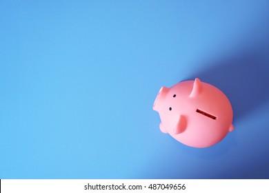 piggy bank save coin, blue desk background, copy space on Left side