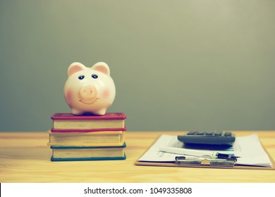piggy bank save coin on book stack calculator business plan and pen on wooden desk table on a gray background, saving money finance concept,selective focus, with copy space