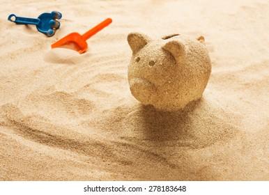 Piggy bank sculpted in sand on sandy beach