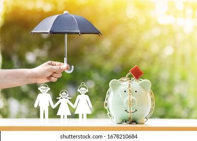 El banco Piggy con seguridad y cerradura y la mano de la familia y la mujer sostienen el paraguas negro para protegerlo a la luz del sol en el parque público, para evitar activos y ahorrar dinero para comprar el concepto de seguro de salud.