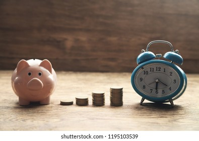 Piggy bank, stack of coins and alarm clock on wooden table. Time to invest your savings