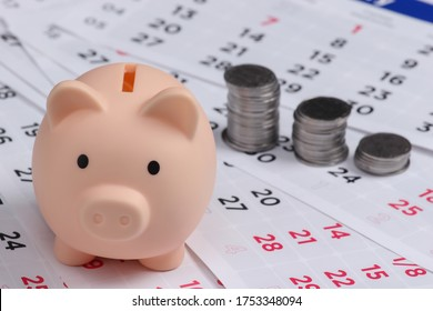 Piggy bank and stack of coins on monthly calendar, saving money, wealth and financial for investment