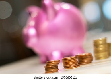 Piggy bank and stacks of money coins. Selective focus