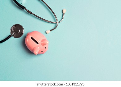 Piggy bank with stethoscope on blue background. Top view with copy space. Concept for financial checkup or saving for medical insurance costs.