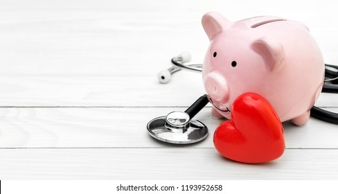 Piggy bank with stethoscope and red heart on white wooden table. Space for text.